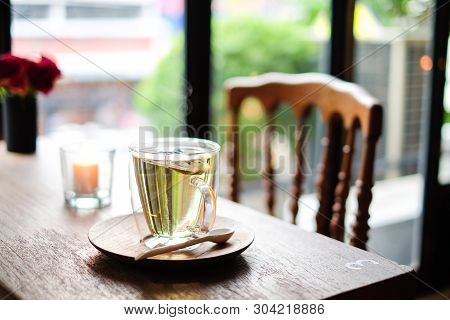 In Coffee Shop, The Hot Lavender Tea In Glass Serve With Wooden Spoon & Saucer On The Table With Cha