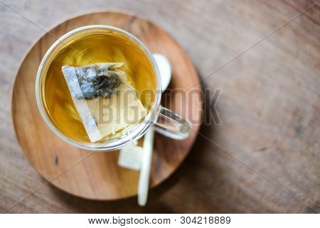 In Coffee Shop, The Hot Lavender Tea In Glass Serve With Wooden Spoon & Saucer On The Table For Rela