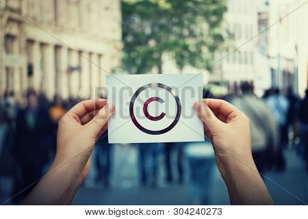 Hands hold paper with copyright symbol. International legal rights intellectual property sign, patent protection. Copyleft trademark license. Creation ownership against piracy crime law infringement. poster