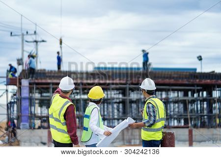 Foreman 3 People Are  See A Blueprint About The Factory Building Structure On The Job Site.foreman,