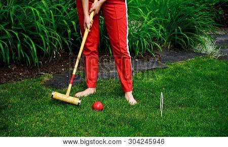 Person Striking Red Croquet Ball Through Wicket