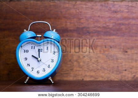 Heart Shaped Alarm Clock On Wooden Background. Time Is Ten O Clock