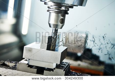 milling cnc machine at metal work industry. Multitool precision machining. Shallow depth of view on shavings