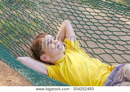 Boy Lying In A Hammock And Dream. The Child Resting In The Garden