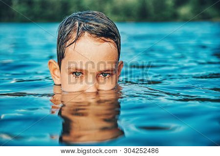 Portrait Of A Child In The Water. Boy With Beautiful Eyes Swimming In A Pond