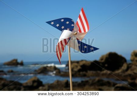 American Flag pin wheel at the beach. American Flag Pinwheel in the sand on a beach.