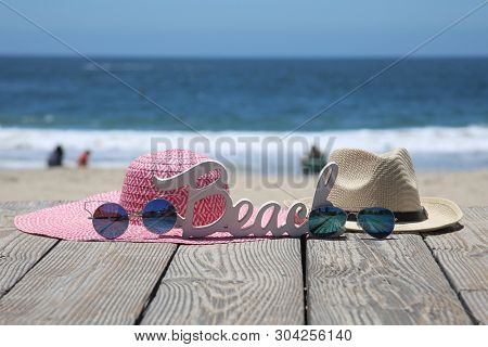 Summer Beach Scene. Sun Hats, Sun Glasses and a BEACH Sign. Beach Board walk with fashion clothes at the beach.