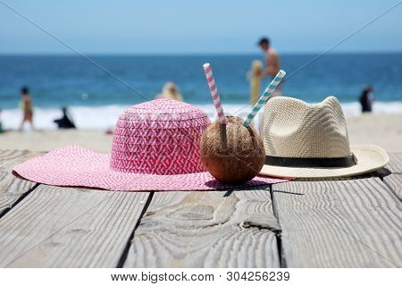 Beach Vacation. Sun Hat. Beach scene. Summer accessories. Summer concept. Coconut with a straw to drink fresh Coconut Juice.