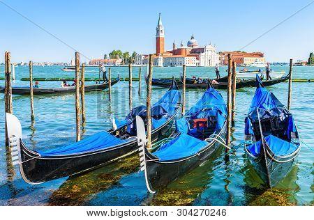 Gondolas In Venice, Italy. Beautiful View Of Venice From San Marco Embankment. Gondola Is Romantic T