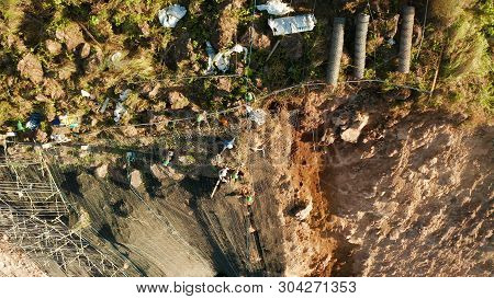 Workers strengthen the slope of the mountain with metal mesh preventing rockfall and landslide on the road, above view. workers constructing anti-landslide concrete wall prevent protect against rock slides. safety concept poster