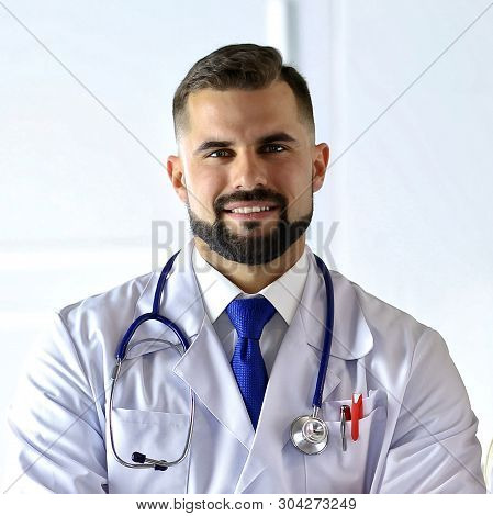 Handsome smiling male doctor. Intelligent expert of a clinic. Man practitioner with a stethoscope. Confident physician. Healthcare worker. Successful medic. Medical staff. Medical career poster
