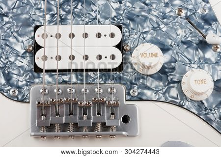Close Up Of Bridge And Humbucker And Controls On White White Electric Guitar, Studio Shoot.