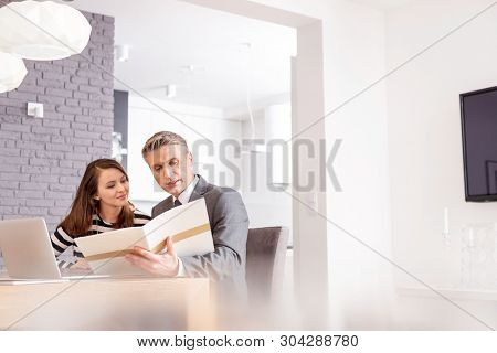 Mature male realtor and female buyer reading document while sitting at table in apartment