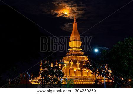 Golden Pagoda, The Architecture Of Laos, Phra That Luang At Night  Bright Illuminated Large Moon.wit