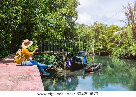 Asian Woman Travel Nature. Travel Relax. Using Mobile Phone Take A Boat Photo. Sitting And Watching
