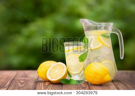 Lemonade In Glass And Jug On Wooden Table Outdoors. Summer Refreshing Drink. Cold Detox Water With L