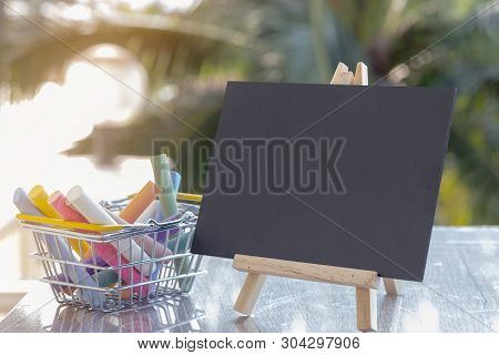 Image Of Empty Small Chalkboard On Wooden Easel And Colorful Chalk Sticks In Basket Over Wooden Tabl