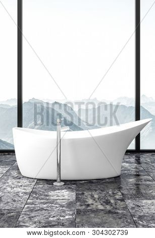 Modern freestanding white bathtub on grey marble floor in front of tall floor to ceiling view windows overlooking rugged mountain peaks. 3d rendering