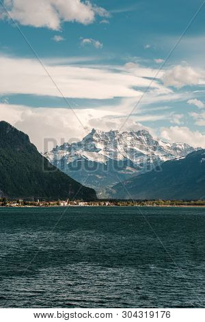 Panoramic View Of Dramatic Evening Clouds Over Lake Geneva In Switzerland With Snow Capped Mountains