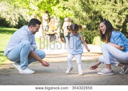 Happy Hispanic Family Skipping Rope Together Outdoors.