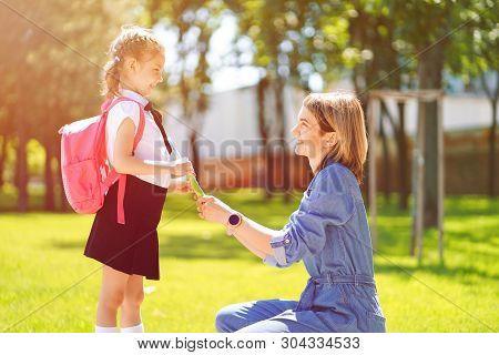 First Day At School. Mother Leads A Little Child School Girl In First Grade. Woman And Girl With Bac