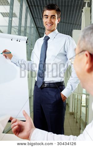 Smiling businessman presenting new strategy to his senior associate