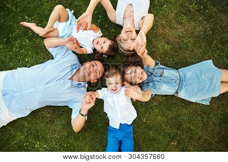 Happy Playful Family Lying On Grass Outdoors. Parents With Children In The Summer. Mom, Dad And Kids