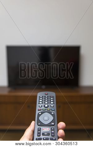 Belgrade, Serbia - May 9, 2019: Hand Holding An Netflix Remote Control. Netflix Is An American Media