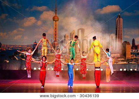 SHANGHAI, CHINA - NOV 28: World famous Shanghai acrobats perform for tourist on stage on Nov 28, 2011 in Shanghai, China. The acrobatic performers were trained from the early age of 6 or 7 years old.