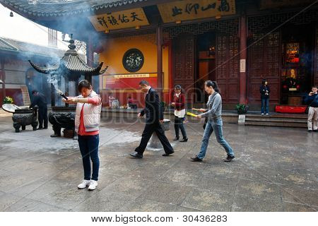 SHANGHAI - NOV 28: Devotees light up joss-sticks to pray at the Jade Buddha Temple (founded 1882) on November 28, 2011 in Shanghai, China. Buddhism is enjoying a revival in modern liberal China.