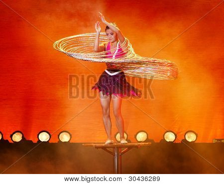 SHANGHAI, CHINA - NOVEMBER 28: A gymnast from the world famous Shanghai acrobats performs a balancing act with many hula hoops for tourist on stage on November 28, 2011 in Shanghai, China.