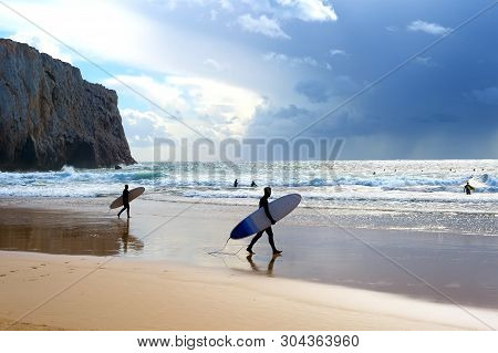 Surfers With Surfboards On The Beach. Rain In The Ocean. Algarve, Portugal