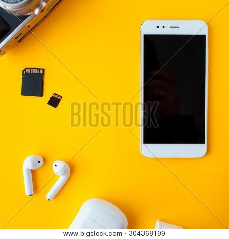 Smartphone And Wireless Headphones. Mobile Phone And Accessories On Yellow Background