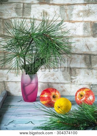 Apples And Lemon On A Wooden Plank Background, In The Background In A Waddling Pine Branch