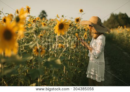 Portrait Of Young Woman In White Dress And Hat Holding A Sunflower In A Sunset Field. Summer Vacatio