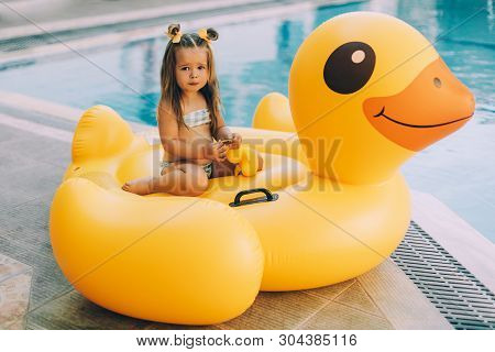 Cute Little Baby-girl With Long Hair Holding A Yellow Duck. In The Background Is An Inflatable Swimm