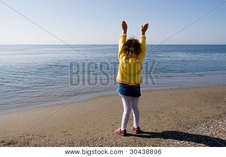 The girl stands at the sea having lifted upwards hands.