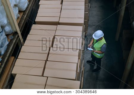 Top View Of Young Warehouse Worker Man With Safety Hard Hat Is Checking Order Details With A Digital