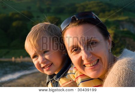 The grandmother with the grandson has a rest at the sea in beams of the leaving sun.
