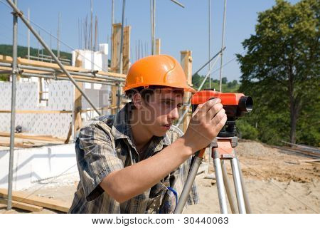 Chief of construction on a building site, looks in a level.