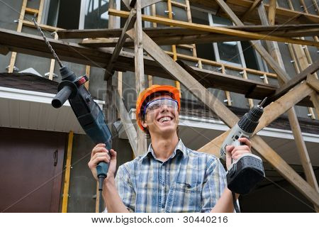 The building worker holds manual drills in hands.