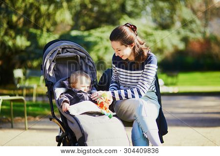 Young Woman With Toddler Girl In Pushchair Walking Together In Luxembourg Garden Of Paris, France. M