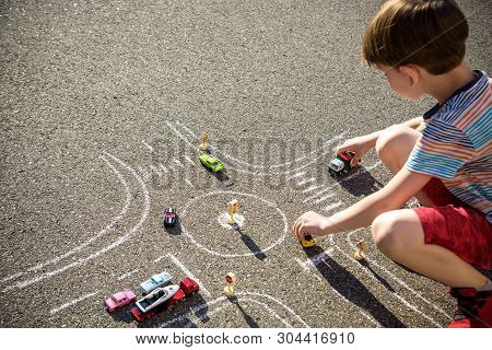 Funny Kid Boy Having Fun With Picture Drawing Traffic Car With Chalks. Creative Leisure For Children
