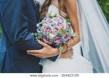 Wedding Day, The Bride And Groom Are Holding A Wedding Bouquet, Faces Are Not Visible