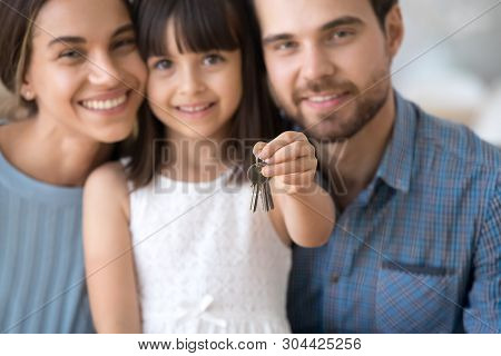 Excited Young Family With Kid Hold Keys Become Homeowners