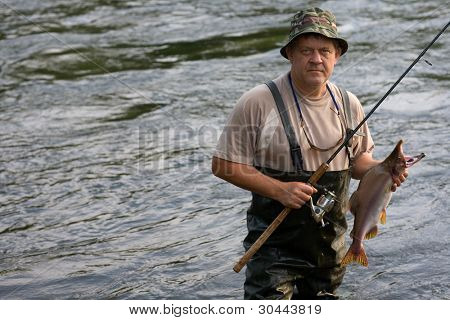Fisherman caught a salmon (pink salmon) on the River. Early Morning.