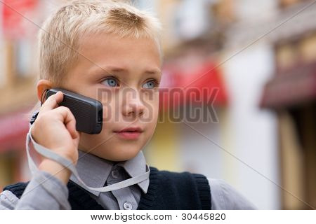Little boy talking on a cell phone on the street.