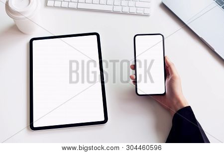 Woman Holding Smartphone And Tablet Mockup Of Blank Screen On The Table.
