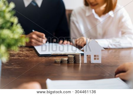 Couples Signed A Contract To Buy A House From The Broker. Coin To Stack Money And Model Houses Place