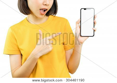 Happy Smiling Woman Pointing With Hand And Finger To Smart Phone With Amazed For Success. Copy Space